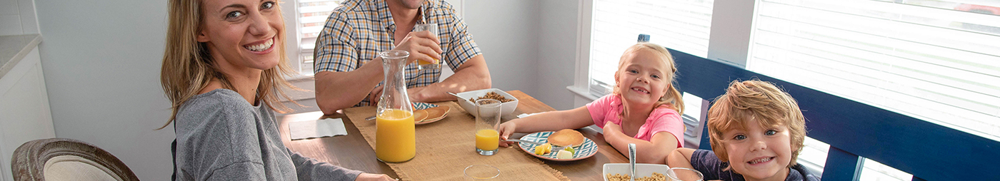 family eating breakfast with orange juice